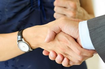 Businessman,And,Woman,Shake,Hands,As,Hello,In,Office,Closeup.